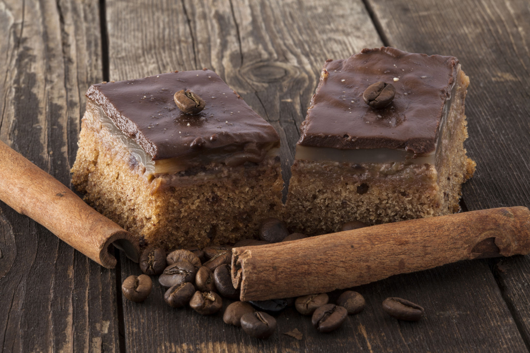 Two chocolate tarts with coffee beans and cinnamon sticks, shot closeup, against a wooden surface. Simply delicious!